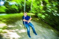 Boy has fun going on the swings Stock Image
