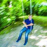 Boy has fun going on the swings Royalty Free Stock Images