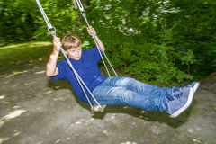 Boy has fun going on the swings Stock Photography