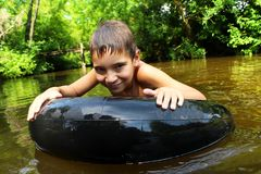 The boy has fun on an tubing in the river. The boy has fun on an inflatable tubing in the river stock image