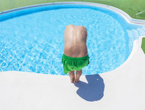 boy has fun jumping in the outdoor pool Stock Photos