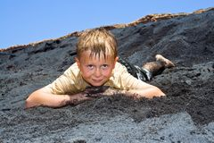 Boy has fun lying in the  black beach Stock Image