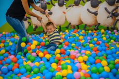 A boy with mother in the playing room with many little colored balls Royalty Free Stock Photo