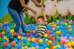 A boy with mother in the playing room with many little colored balls Stock Photos