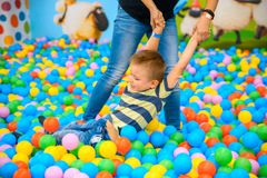 A boy with mother in the playing room with many little colored balls Stock Photography