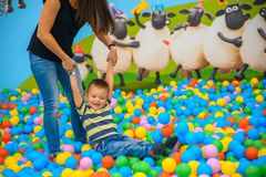 A boy with mother in the playing room with many little colored balls Stock Photo
