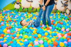 A boy with mother in the playing room with many little colored balls Stock Images