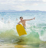 Boy has fun in the ocean with his boogie board. Boy has fun in the waves of the ocean with his boogie board Royalty Free Stock Images
