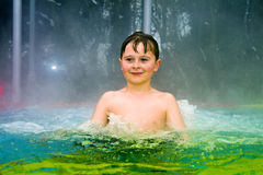 Boy has fun in the outdoor thermal pool in winter Royalty Free Stock Image
