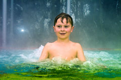 Boy has fun in the outdoor thermal pool in winter Stock Photography