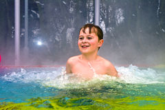 Boy has fun in the outdoor thermal pool in winter Royalty Free Stock Photography