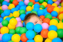 A boy in the playing room with many little colored balls Stock Photo