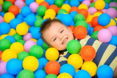 A boy in the playing room with many little colored balls Royalty Free Stock Images