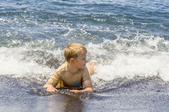 Boy has fun playing in the waves Royalty Free Stock Image