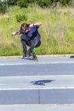 Boy has fun riding his push scooter Stock Photo
