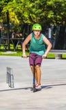 Boy has fun riding his push scooter Royalty Free Stock Photo
