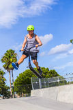 Boy has fun riding his push scooter Stock Images