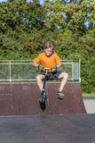 Boy has fun riding push scooter at the skate park Royalty Free Stock Images