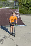 Boy has fun riding push scooter at the skate park Royalty Free Stock Photo