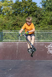 Boy has fun riding push scooter at the skate park Stock Images
