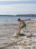 Boy has fun running with surfboard in the waves royalty free stock images