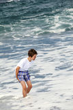 Boy has fun in the spume at the black  beach Royalty Free Stock Photography