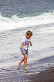 Boy has fun in the spume at the black beach Royalty Free Stock Photos