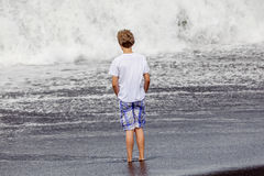 Boy has fun in the spume at the black volcanic beach Royalty Free Stock Images