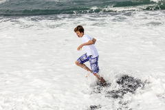 Boy has fun in the spume at the black volcanic beach Stock Images
