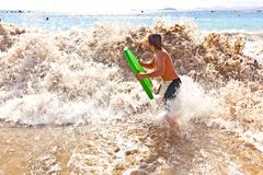 Boy has fun with the surfboard Stock Images