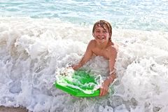Boy has fun with the surfboard Royalty Free Stock Photos