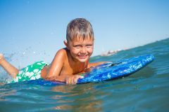 Boy has fun with the surfboard Stock Photos