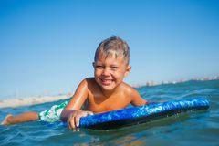Boy has fun with the surfboard Royalty Free Stock Photography
