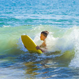 Boy has fun surfing in the waves Stock Photos