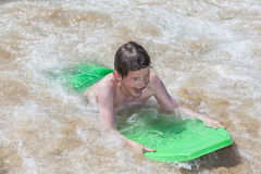 Boy has fun surfing in the waves royalty free stock photo