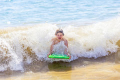 Boy has fun surfing in the waves Stock Images