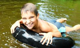 The boy has fun on an tubing in the river. stock image