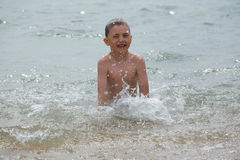 The boy has a fun in water Royalty Free Stock Image