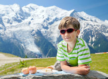 The boy has got pic nic on top of mountain. The boy has got pic nic against snowy mountains summits royalty free stock photos