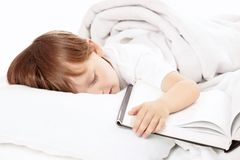 Boy has got tired. Little boy sleeps in bed embracing the book, isolated stock photography