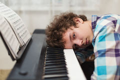 The boy has got tired to play the piano. The boy has fallen asleep on the piano keyboard royalty free stock photo