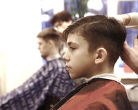 Boy has his hair cut in barber shop men room Royalty Free Stock Photography