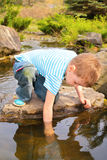 Boy has lowered  hand in  stream Stock Image