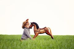 A little boy cuddle to wooden rocking horse. A boy has three years old, wearing grey sweater,nstraw hat, take care his pet, dreaming obaut a real horse. a Royalty Free Stock Images