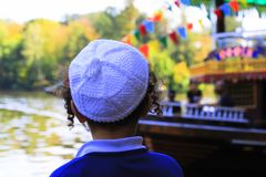 The boy hasidic looks at the pleasure ship in the lake in Uman, Ukraine, the time of the Jewish New Year. Rosh-ha-Shana royalty free stock photo