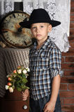 Boy in a hat and a bouquet of flowers Stock Photography