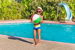 Boy in hat holding ball standing near pool Royalty Free Stock Images