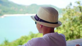 The boy in the hat looking into the distance the sea and mountains from the viewpoin. view stock footage