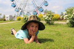 A boy in a hat lying on the grass in the Park royalty free stock photos