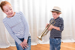 Boy with hat is playing the trumpet - sister annoyed Stock Photos